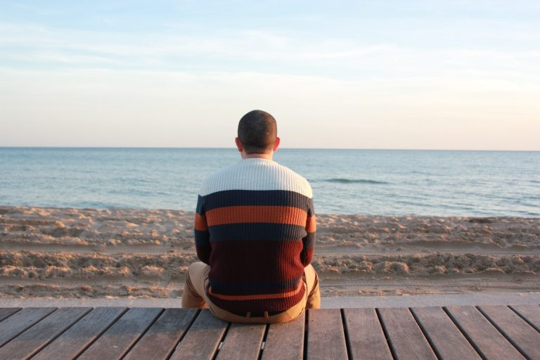 man-sitting-alone-at-the-beach