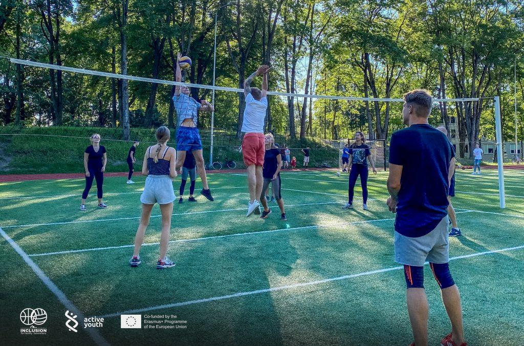 Grupė jaunų žmonių žaidžia tinklinį lauke, tinklinio aikštelėje. Du žmonės iš skirtingų komandų pašokę į viršų ir taiko į kamuolį