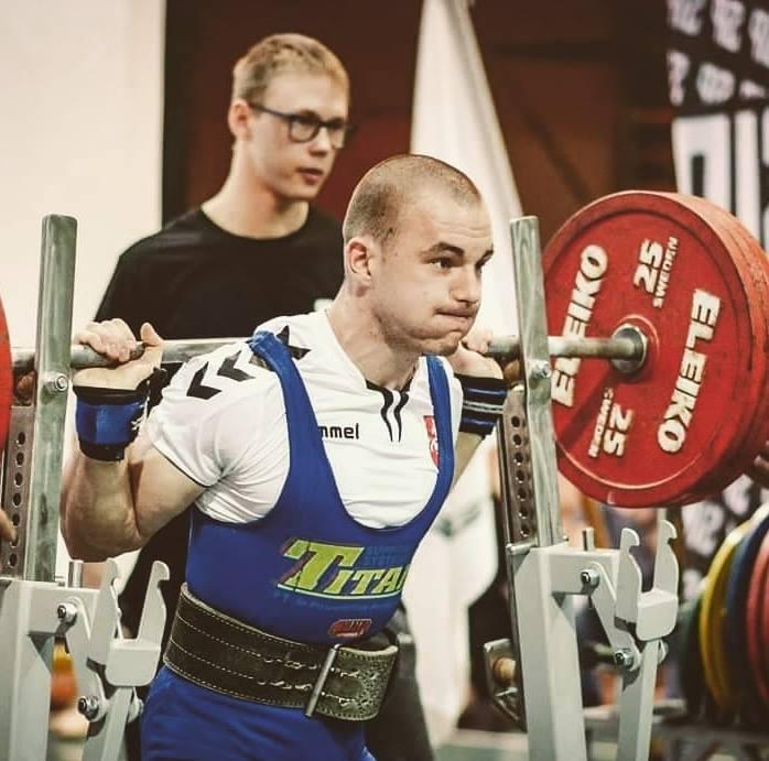 Sportininkas kelia svorį sporto salėje
