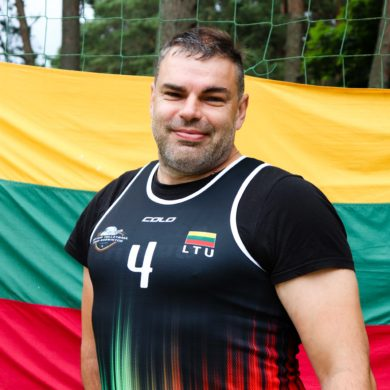 a sportsman standing. Lithuanian flag is behind him