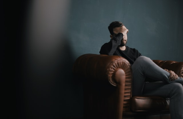 man struggling with mental healthsitting on a couch with a hand on his head