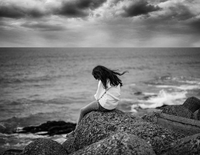 moteris sėdi ant akemns krašto audringos jūros pakrantėje