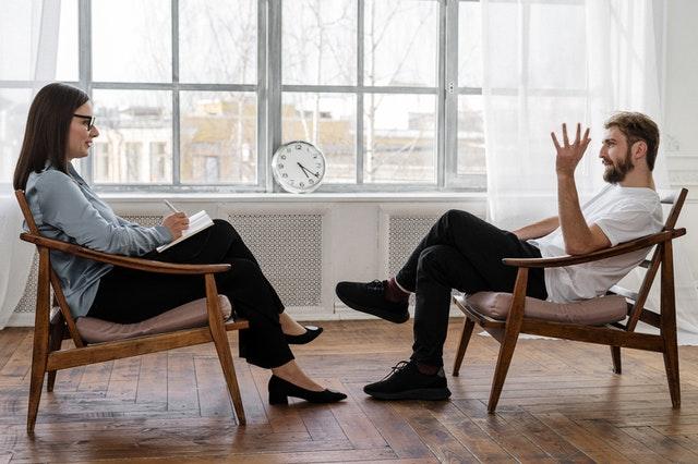 ŽIV konsultacija. vyras ir moteris sėdi vienas priešais kitą ant kėdžių dideliame kambaryje. Moteris klauso vyro, ant jos kelių yra užrašinė. Vyras iškėlęs ranką pasakoja