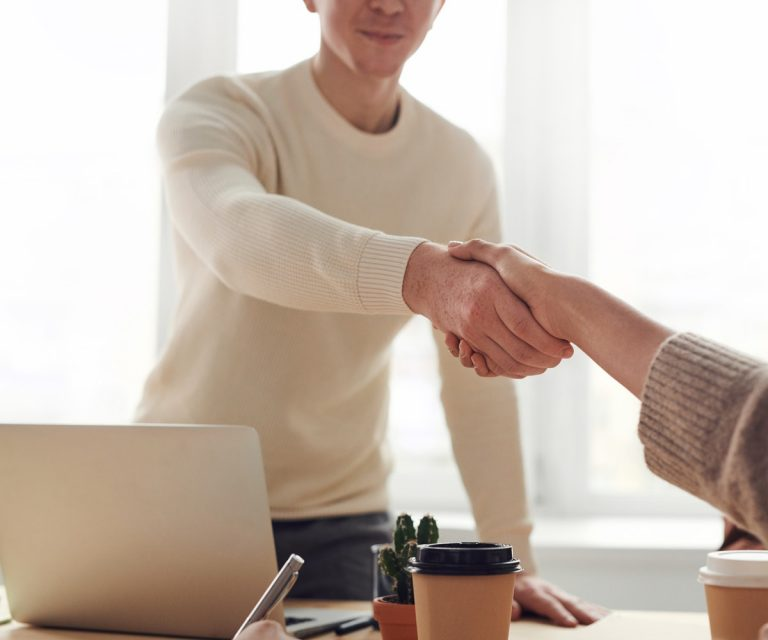 young man shaking hands with other person